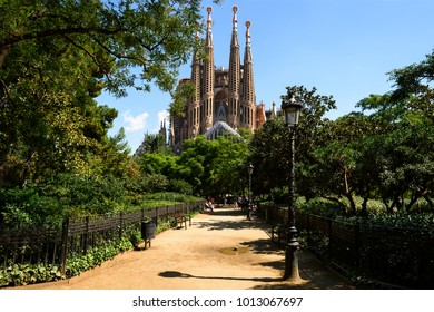 Barcelona, Spain - August 23. 2017: Impressive view of La Sagrada Familia, greatest Gaudi masterpiece and city park green trees, street light and path to building which still unfinished since 1882.