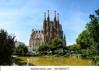 Barcelona, Spain - August 25. 2017: Impressive view of La Sagrada Familia, greatest Gaudi masterpiece in front of pond and green trees, building still unfinished since 1882. Barcelona, Spain