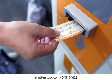 BARCELONA, SPAIN - AUGUST 6, 2016. Man validating ticket in punching machine for the train in Barcelona, Spain.