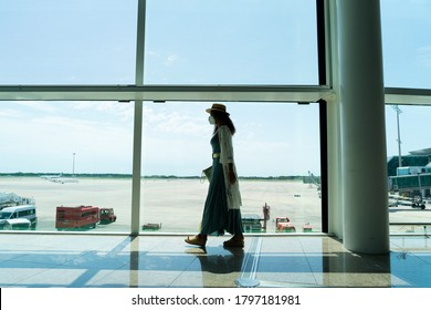 BARCELONA; SPAIN - AUGUST 8th 2020: Barcelona airport with very few people due to the new coronavirus outbreaks in the middle of August. Woman walking towards the boarding gate.
