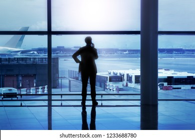 Barcelona- Spain- Circa July 2018. Businessman silhouette calling phone in front of glass windows at Barcelona airport lobby