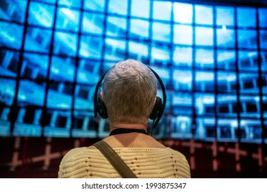 Barcelona- Spain- Circa November 2019. Senior woman with headphones in front of multimedia screen projection. Shallow focus on background