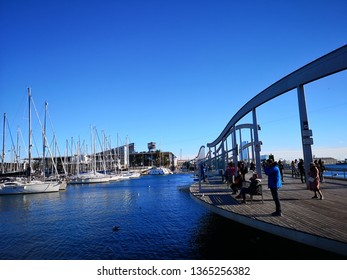 Barcelona, Spain - December 19, 2018: It's just a wooden walkway or a bridge at the marina: the Rambla del Mar. The impressive wave-like construction of the bridge makes it a magnet for visitors.