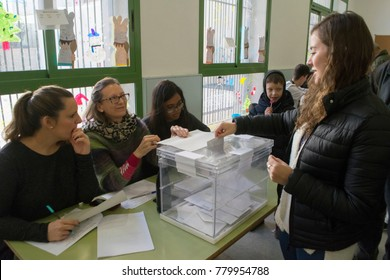 BARCELONA, SPAIN - DECEMBER 21, 2017: Woman placing a her vote into the ballot box during Catalonia's regional election.