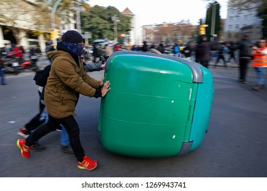 Barcelona / Spain - December 21, 2018: demonstrators prepare barricades while anti clash riots police charge during the protest against the celebration of the Spanish ministers council in Barcelona