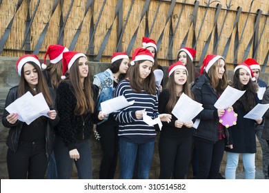BARCELONA, SPAIN - DECEMBER 22, 2014: A group of young, singing Christmas carols in front of an entrance of La Sagrada Familia.
