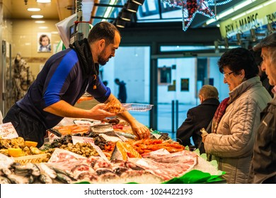 Barcelona, Spain - December 5, 2016: Vendor sells fish and seafood on the Santa Catarina Market, located in the neighborhood of Sant Pere and is the oldest covered market in Barcelona, Spain.