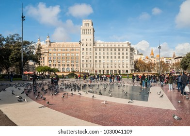 Barcelona, Spain - December 5, 2016: Tourists feed the pigeons on the Square of Catalonia (Placa de Catalunya) in Barcelona. Plaza de Catalunya is one of the main attractions of the Catalonia capital.