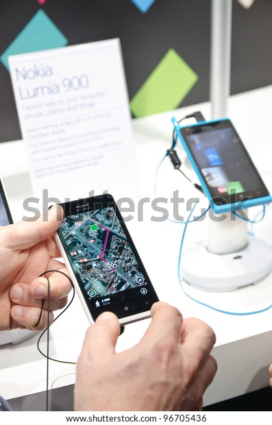 BARCELONA, SPAIN - FEB 26: Visitor of the GSMA MWC 2012 tests the new Nokia Lumia 900 at the Nokia exhibition stand on Feb 26, 2012 in Barcelona, Spain