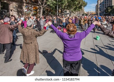 Barcelona, Spain - February 03, 2013: People holding hands and dancing national dance Sardana in Barcelona. It is a type of circle dance typical of Catalonia.