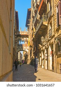 BARCELONA, SPAIN - FEBRUARY 15, 2018:  People walk under the neogothic bridge at Carrer del Bisbe (Bishop Street) in the famous Gothic Quarter. Barcelona, Catalonia, Spain
