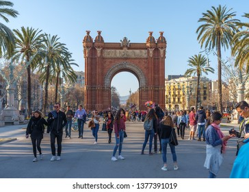 Barcelona, Spain - February 23, 2019: People are strolling through an alley between the Arch of Triumph and Ciutadella park in Barcelona, Spain
