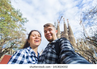 BARCELONA, SPAIN - FEBRUARY 6, 2018: Happy tourists photographing in front of the famous Sagrada Familia roman catholic church in Barcelona, architect Antoni Gaudi
