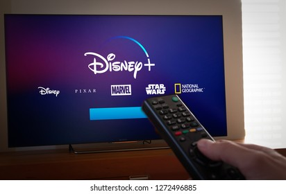 Barcelona, Spain. Jan 2019: Man holds a remote control With the new Disney+ screen on TV. Disney+ is an online video streaming subscription service, set to launch in the US in September.Illustrative