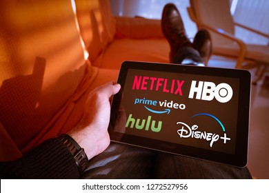 Barcelona, Spain. Jan 2019: Man holds a tablet with Netflix hulu, amazon video, HBO and Disney+ logos on screen.Disney + is set to compete with other video streaming subscription services.Illustrative