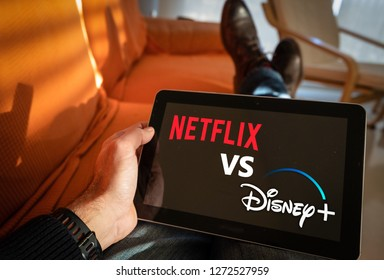 Barcelona, Spain. Jan 2019: Man holds a tablet with Netflix vs Disney+ application logo on screen.Disney + is set to compete with other video streaming subscription services like Netflix,.Illustrative