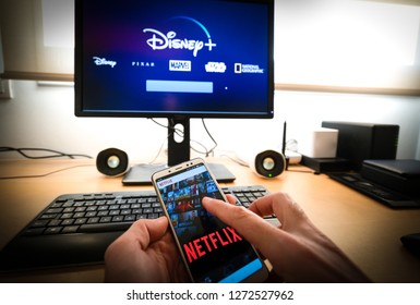 Barcelona, Spain. Jan 2019: Man holds a smartphone with netflix app and a Pc with the new Disney plus on screen on the background. Disney + is set to compete with other video streaming subscription