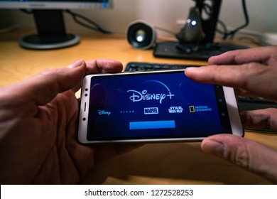 Barcelona, Spain. Jan 2019: Man holds a smartphonewith the new Disney plus on screen . Disney+ is an online video streaming subscription service, set to launch in the US in September.Illustrative