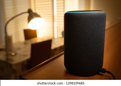 Barcelona, Spain. January 2019: Selective focus on Amazon Echo Plus smart Home device turning on a floor lamp with Alexa voice control. Illustrative editorial