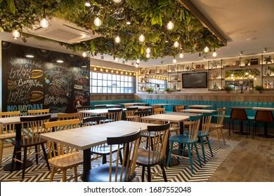 Barcelona, Spain - January 2020: Alaska. Elegant and modern restaurant with wooden walls and ceramic floors. Interior design restaurant