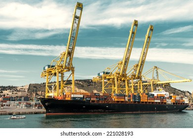 BARCELONA, SPAIN - JANUARY 29: Cargo unloads its containers on the deck of Barcelona commercial harbor on January 29, 2014