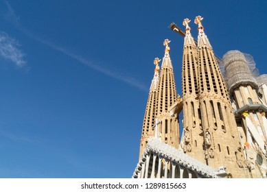 Barcelona, Spain – January 4, 2019: Basilica Of The Sagrada Familia on bright blue sky. Famous Roman Catholic church at sunny day with copy space, place for text. Designed by Antoni Gaudi.