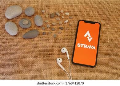 Barcelona, Spain - July 02, 2020; Strava App with Earphone and River Rocks. Strava is a social-fitness network app. Strava