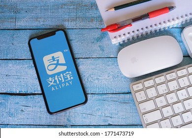 Barcelona, Spain - July 07, 2020; Alipay Iphone Display with Keyboard Mouse and Red Pen. Alipay is a third-party mobile and online payment platform. #Alipay
