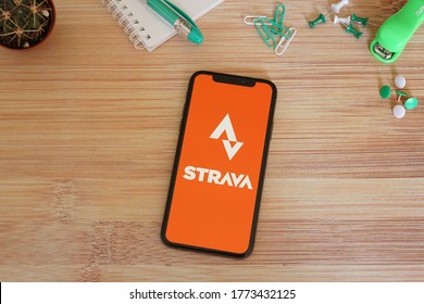 Barcelona, Spain - July 10, 2020; Strava App with Green Stationery on a Bamboo Desk. Strava is a social-fitness network app. #Strava