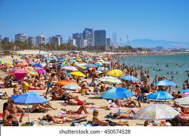 BARCELONA, SPAIN - JULY 10: Sunbathers at Platja del Bogatell beach on July 10, 2016 in Barcelona, Spain, with the Parc del Forum in the background. This busy beach is mainly frequented by the locals