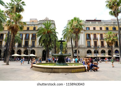 BARCELONA, SPAIN - JULY 13, 2018: Plaza Real with fountain in Barcelona. Plaza Real lies next to La Rambla and constitutes a well-known touristic attraction.