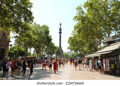 BARCELONA, SPAIN - JULY 13, 2018: people walking in this popular pedestrian area La Rambla with Christopher Columbus statue in the end of the street, Barcelona, Spain