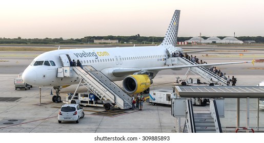 BARCELONA, SPAIN - JULY 16, 2015: Passengers are boarding on a Vueling Airbus A320 in El Prat Barcelona airport. Vueling is a spanish low-cost airline with some 87 planes in operation.