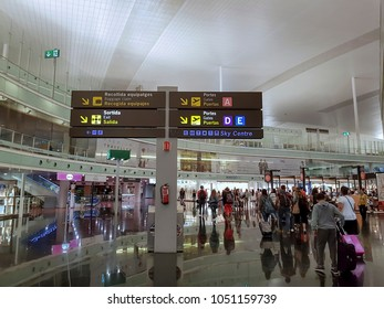 Barcelona, Spain - July 17 2017: El Prat Airport Terminal 1 interior. Passengers inside BCN Aeroport de Barcelona walking along gate info signs and duty free shops.
