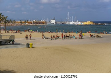 Barcelona, Spain - July 19 2017: Beach with crowd in Catalonia. Sunbathers on benches by a sandy beach on the Mediterranean sea.