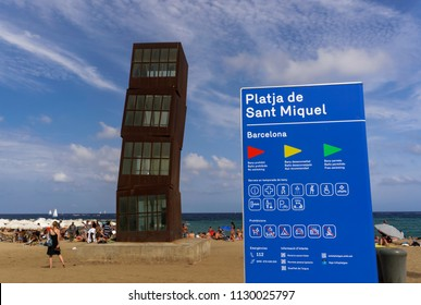 Barcelona, Spain - July 19 2017: Beach in Catalonia with the Wounded Shooting Star sculpture. The Cubes artwork on sandy La Barceloneta beach with crowd and Platja de Sant Miquel beach sign.
