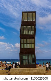 Barcelona, Spain - July 19 2017: Beach in Catalonia with the Wounded Shooting Star sculpture. The Cubes artwork installed on sandy La Barceloneta beach with crowd.