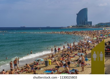 Barcelona, Spain - July 19 2017: Beach with crowd in Catalonia. Bathers on a crowded sandy beach with background view of W sail shaped hotel.