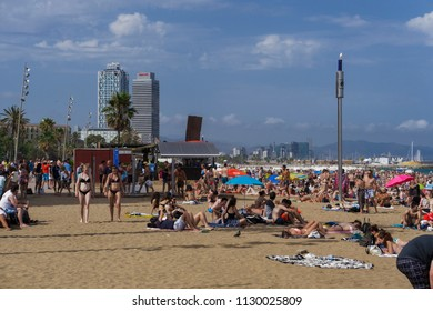 Barcelona, Spain - July 19 2017: Beach with crowd in Catalonia. Bathers on crowded sandy beach with background view of waterfront skyscrapers and buildings.