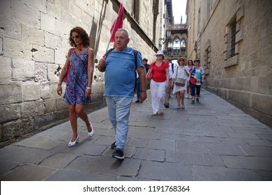 Barcelona, Spain - July 20, 2018: A guide leads tourist along a street in the historic gothic quarters.