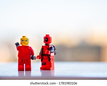 Barcelona, Spain - July, 2020: Two red lego figures one pointing to the straight with angry face and deadpool looking the other miniature. Blurry background.