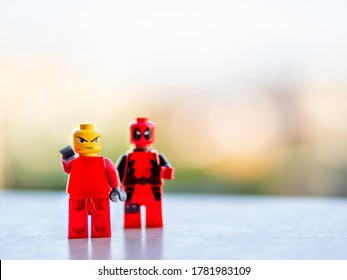 Barcelona, Spain - July, 2020: Two red lego figures stand with angry faces and blurry background. Deadpool and mad face men pointing toys. Copy space for text