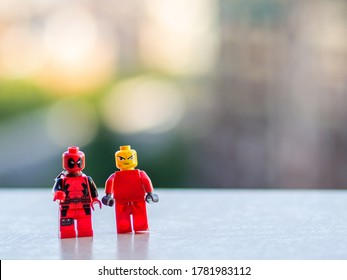 Barcelona, Spain - July, 2020: Two red lego figures stand with angry faces and blurry background. Deadpool and mad face men toys.