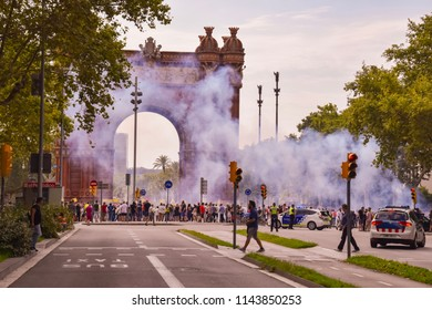 Barcelona, Spain - July 25, 2018: Taxidrivers demonstrate against Uber in front of the Arc de Triomf in Barcelona. They strike and demonstrate with smoke bombs and posters. The police is present.