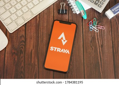Barcelona, Spain - July 27, 2020; Strava App with Stationery on a Brown Wooden Table. Strava is a social-fitness network app. #Strava