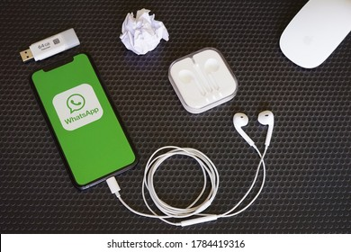 Barcelona, Spain - July 27, 2020; Whatsapp Iphone Display with Earphone and Magic Mouse. WhatsApp Messenger is a freeware, cross-platform messaging and VoIP service. #WhatsApp Messenger