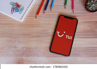 Barcelona, Spain - July 29, 2020; Tui Iphone Screen with Colored Pencils on a Bamboo Table. TUI is the world's leading tourism group.  TUI