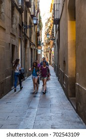 BARCELONA, SPAIN, JULY 5, 2017: Family of four walking along the narrow streets of Barcelona one summer afternoon