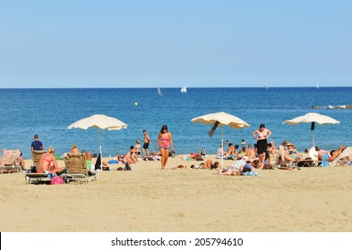 BARCELONA, SPAIN - JULY 6, 2012: Crowds of tourists enjoy the sun on the beach in Barcelona