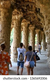 Barcelona, Spain - July 6, 2018: Visitors at the colonnaded footpath in Park Güell, famous landmark designed by Antoni Gaudí.